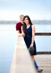 Young interracial couple standing together on wooden pier overlo