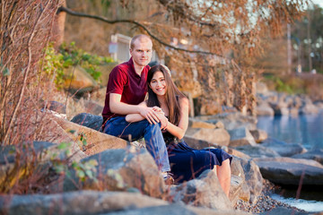 Young interracial couple sitting together on rocky shoreline by