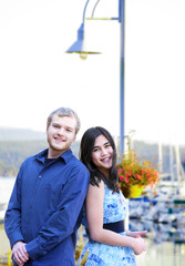 Interracial couple standing by boat pier