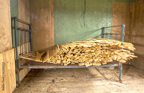 Framework of bed with dumped firewood. HDR