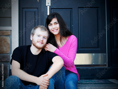 Young interracial couple sitting on front steps