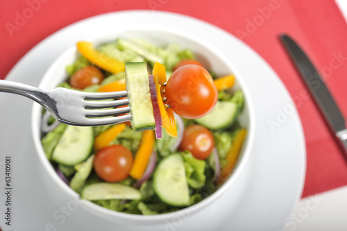 fork with cherry tomato, carrot and cucumber in fresh salad bowl