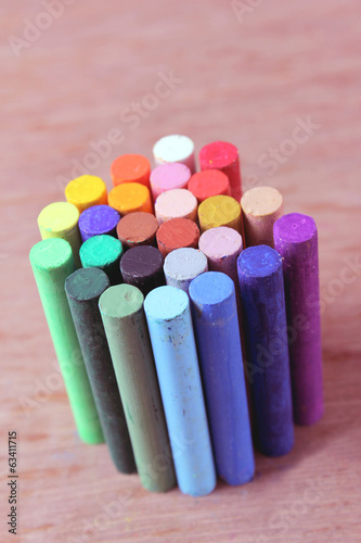 Multicolored crayons on wood background