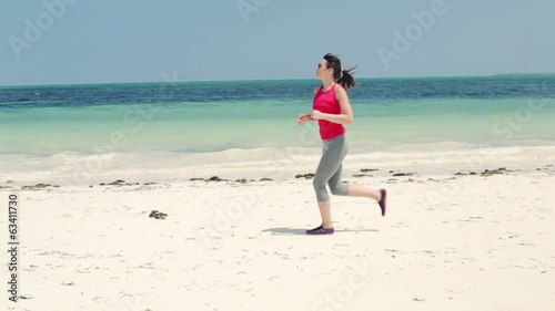 Young woman jogging on exotic beach, slow motion