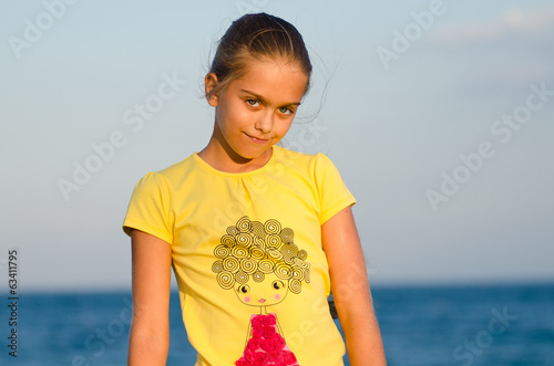 girl in yellow t-shirt on the background of sea sunset