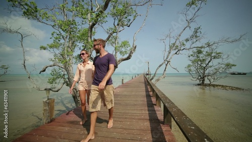 Happy couple walking on wooden pier
