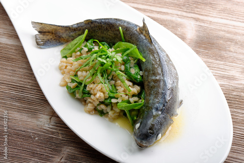 Trout cooked with barley and spinach