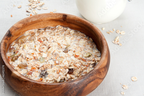 Muesli with milk in wooden bowl