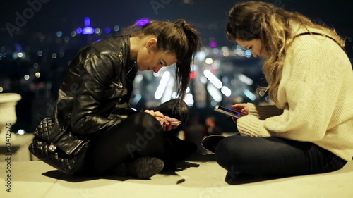 two women sitting on a bench and using their cellphones