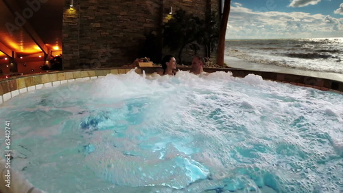 Young Couple in jacuzzi on the tropical spa resort