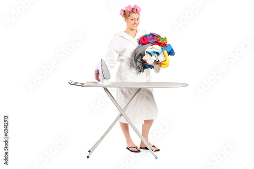 Woman in bathrobe preparing clothes for ironing