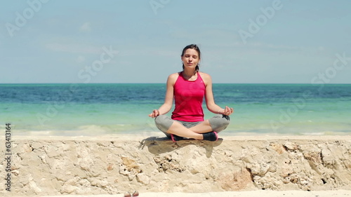 Young beautiful woman meditating by the sea
