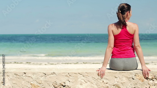 Young sportswoman relaxing on stone wall by the sea