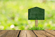 Wooden blackboard sign in grass and bokeh background