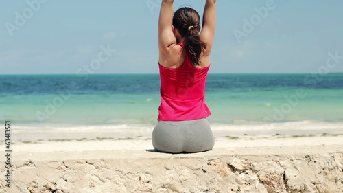 Young sportswoman relaxing, stretching on stone wall by the sea