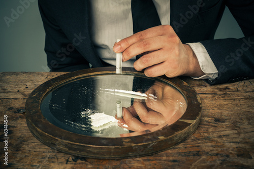 Businessman snorting cocaine