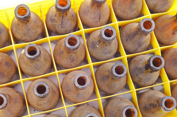 Dusty vintage empty bottles in a yellow beer crate