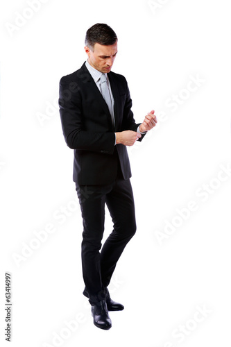 Full-length portrait of a businessman buttoning cuff sleeves