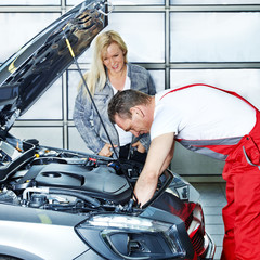 Female customer and car mechanic in a garage