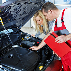 Female customer and car mechanic in a garage