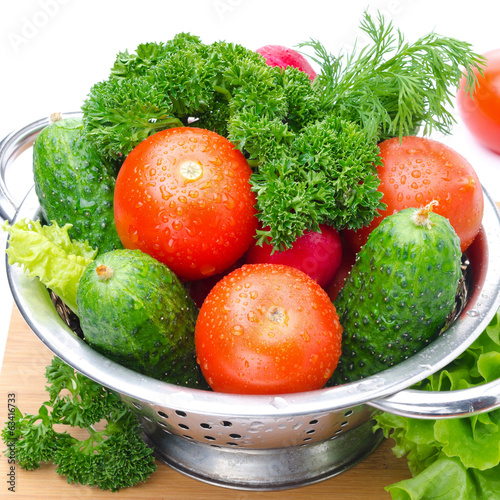 Fresh vegetables and herbs in a metal colander, close-up
