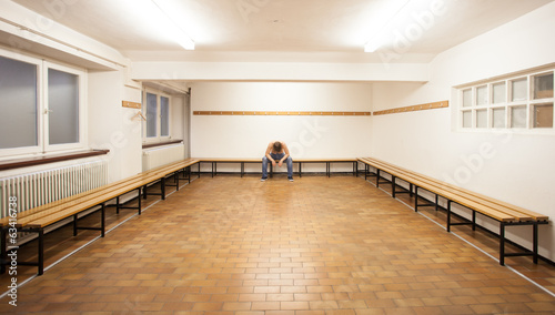 man sitting in empty locker room