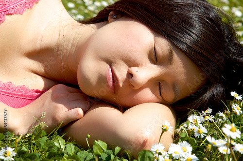Asian girl sleeping in park surrounded by flowers