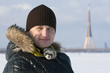 Man with ferret  in winter outdoor