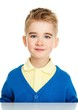 Cheerful little boy in blue cardigan and yellow shirt