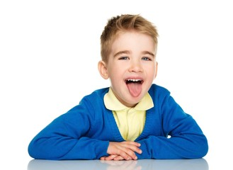 Sly little boy in blue cardigan and yellow shirt showing tongue