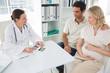 Gynaecologist explaining reports to expectant couple