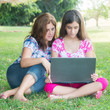 Hispanic girl and her  mother using a laptop outdoors