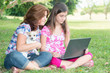 Hispanic girl and her mother browsing the web outdoors