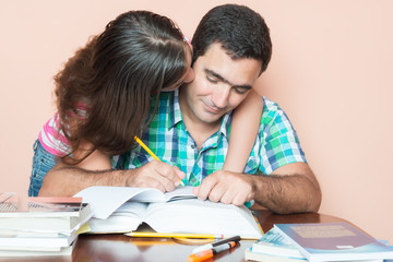 Young man studying with his daughter kissing him