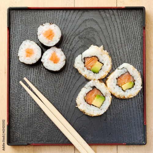sushi rolls  on black plate and chopsticks