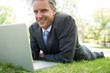 canvas print picture - Businessman with laptop lying in park