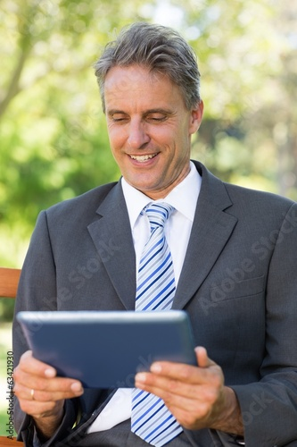 Happy businessman using digital tablet