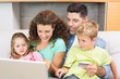 Cheerful family sitting on sofa with laptop shopping online