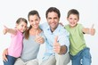 Cute family smiling at camera together showing thumbs up
