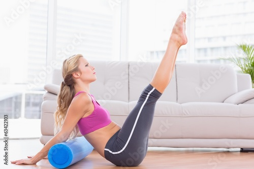 Fit blonde stretching on floor using foam roller