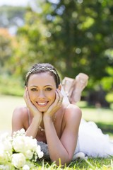 Bride relaxing on grass in the park