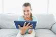 Cheerful woman sitting on couch using tablet pc