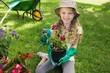 canvas print picture - Smiling young girl engaged in gardening