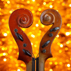 Two vintage violin scrolls on bokeh background