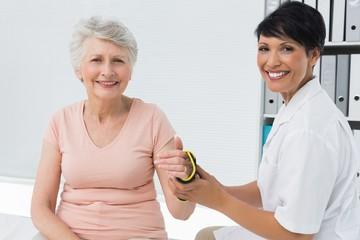 Female doctor fixing wrist brace on senior patients hand