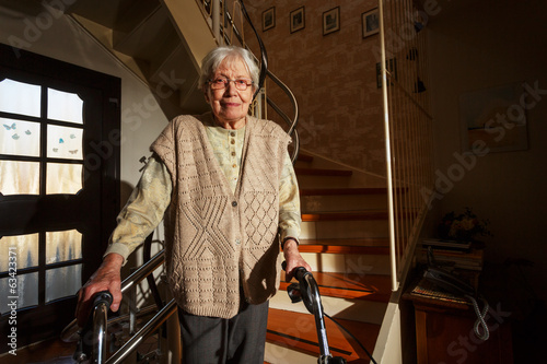 Elderly woman with walking frame in the staircase