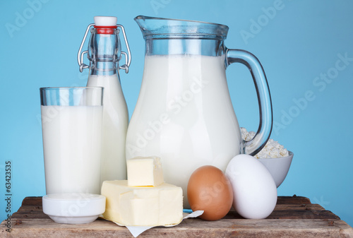 Dairy products assortment on old wooden table, blue background