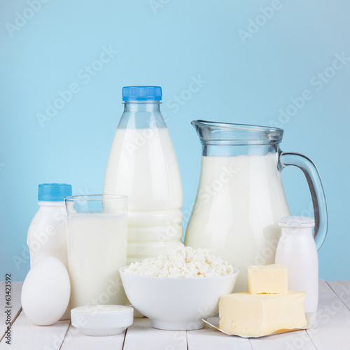 Dairy products assortment on wooden table, blue background