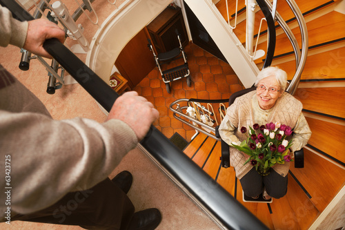 Leinwanddruck Bild elderly couple in the staircase with stairlift