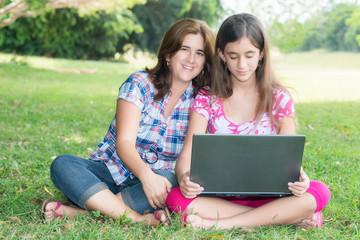 Hispanic girl and her mother using a laptop computer outdoors